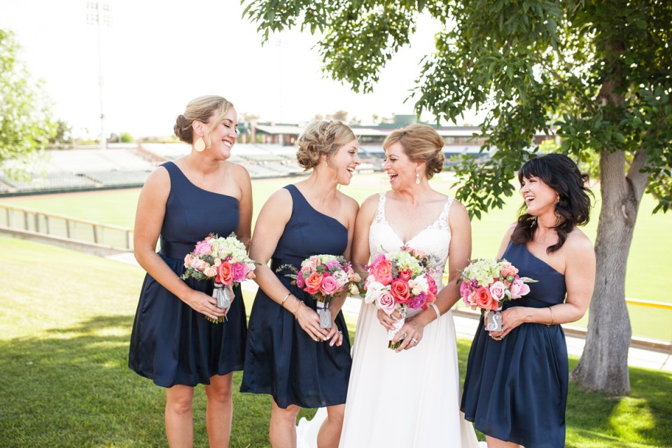 bride with bridesmaids in one shoulder navy blue tea length bridesmaids dresses