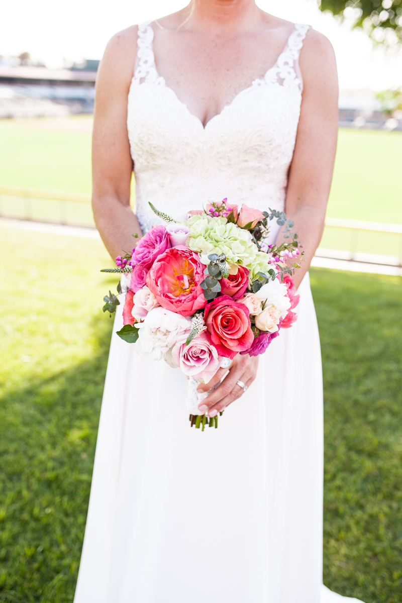 Bride with lace v neck sheath wedding dress with colorful bridal bouquet