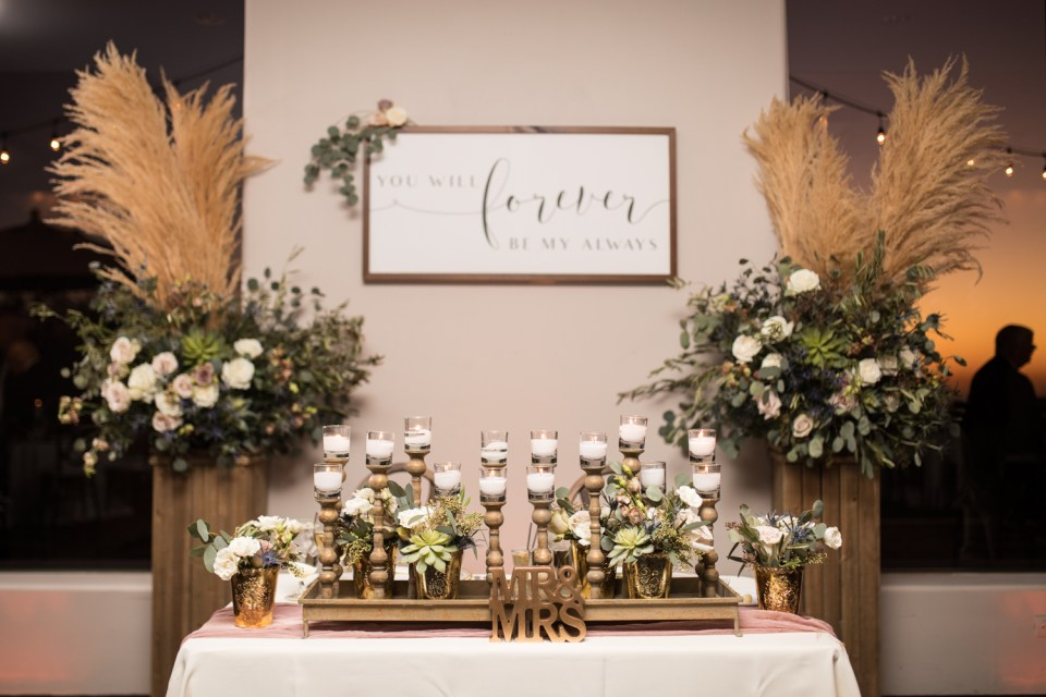 troon north wedding reception sweetheart table with candles and florals