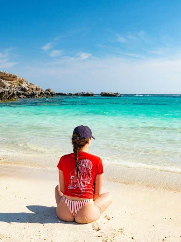 Girl sitting on beach Rottnest Island Perth Western Australia