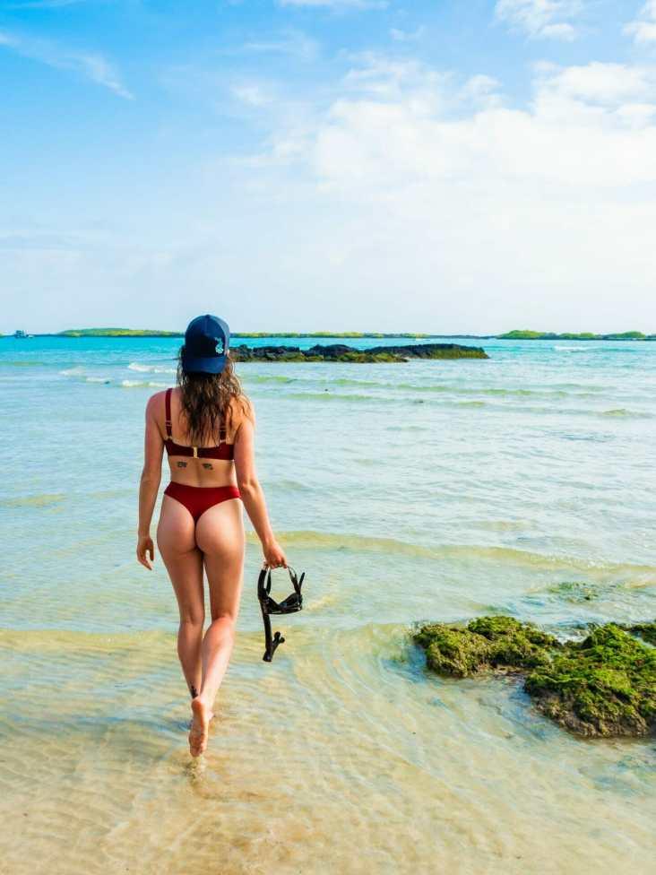 Girl in bikini holding snorkel on beach Isla Isabela Galápagos
