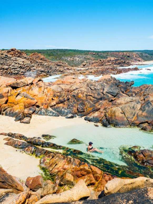 Girl laying in rock pool Injidup Natural Spa Western Australia