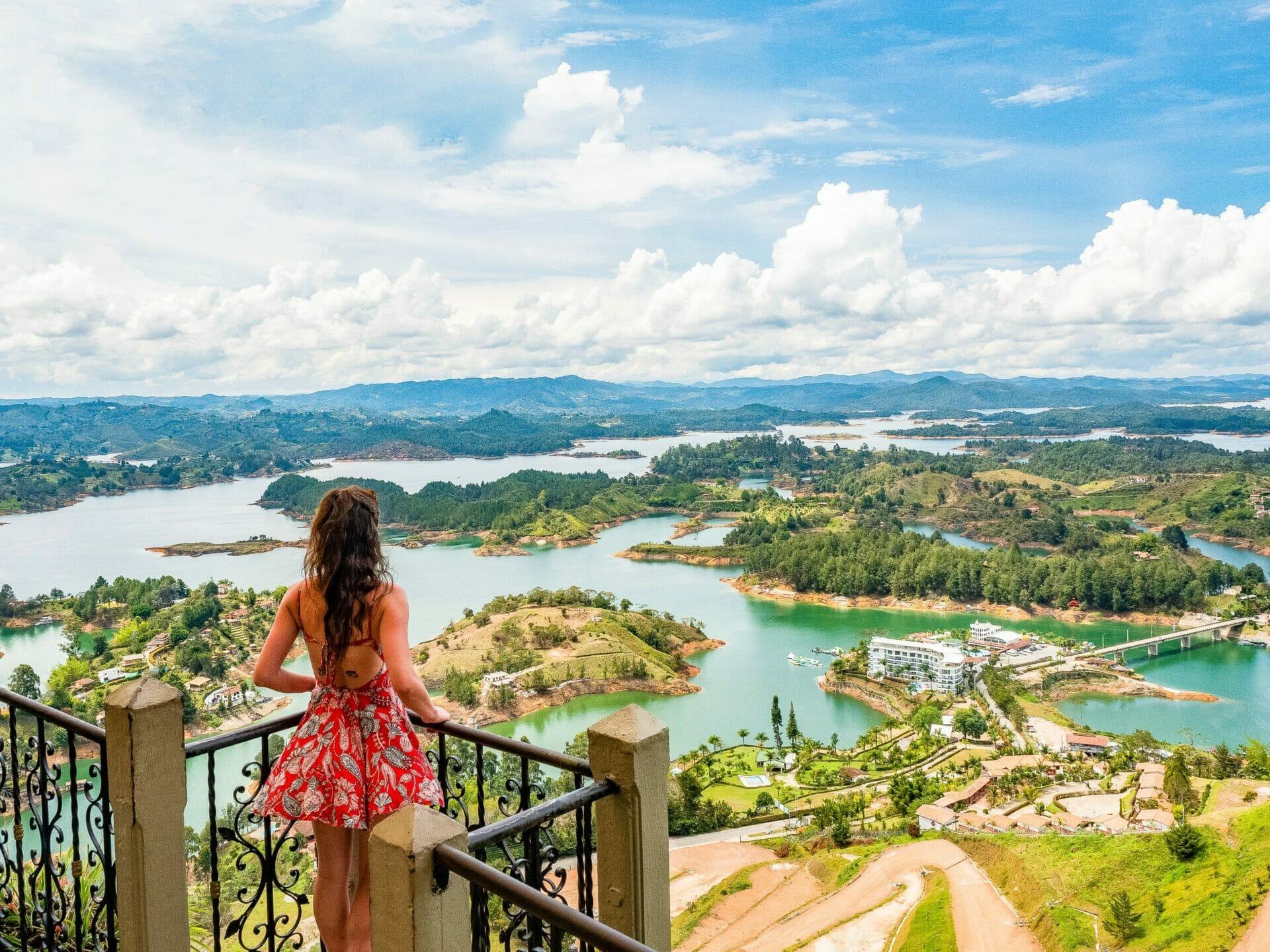 Girl climbing La Piedra overlooking lake Guatapé