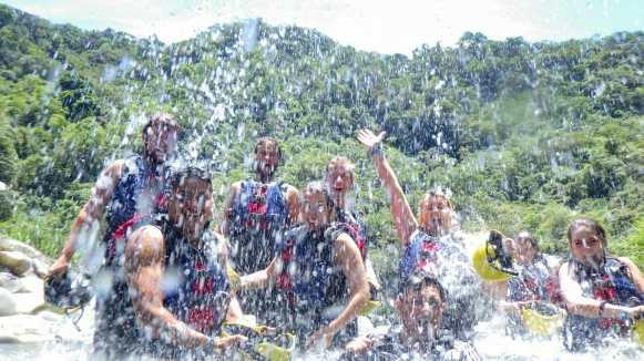 Friends throwing water on river in Baños