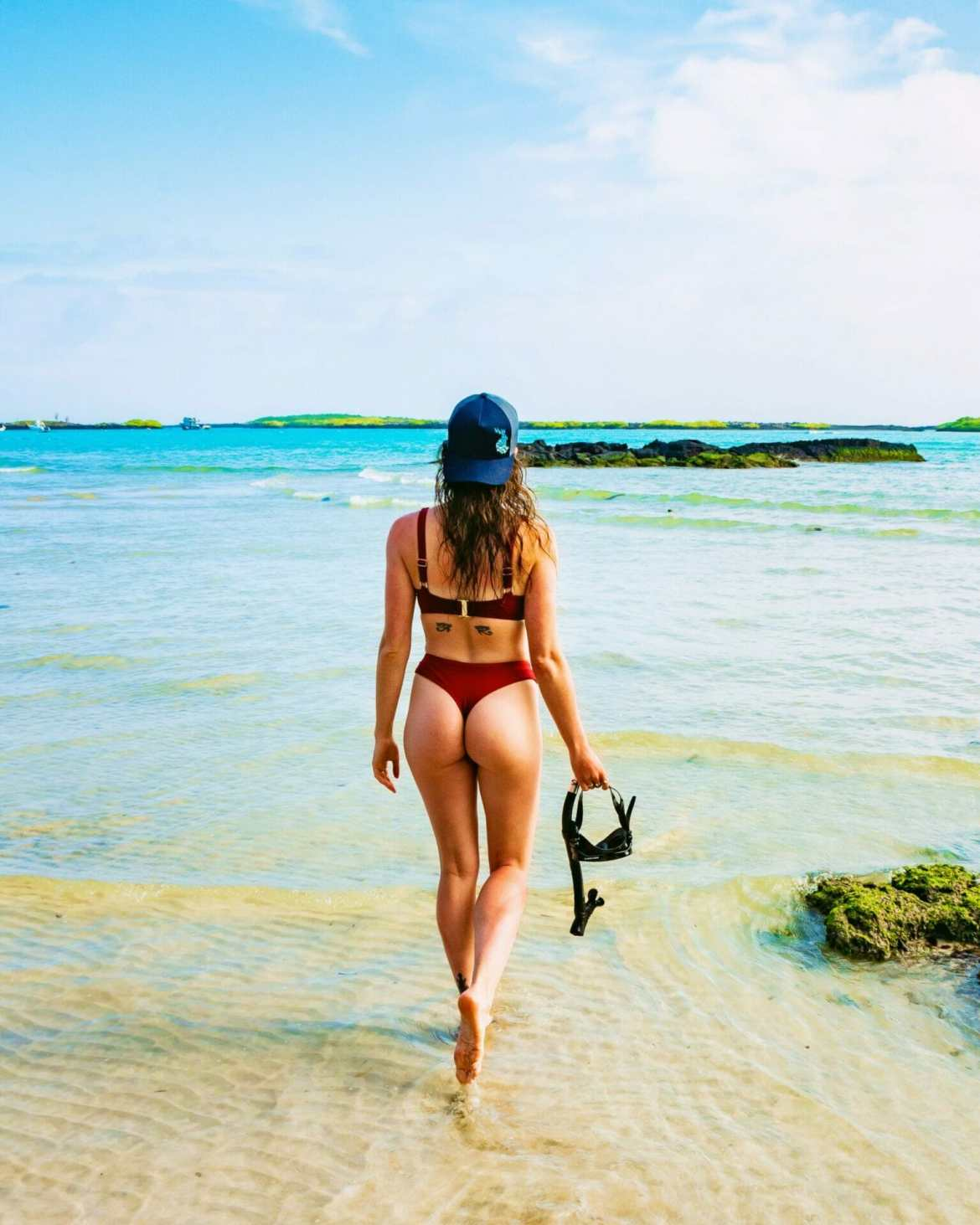 Girl with snorkel walking on beach into ocean Galápagos
