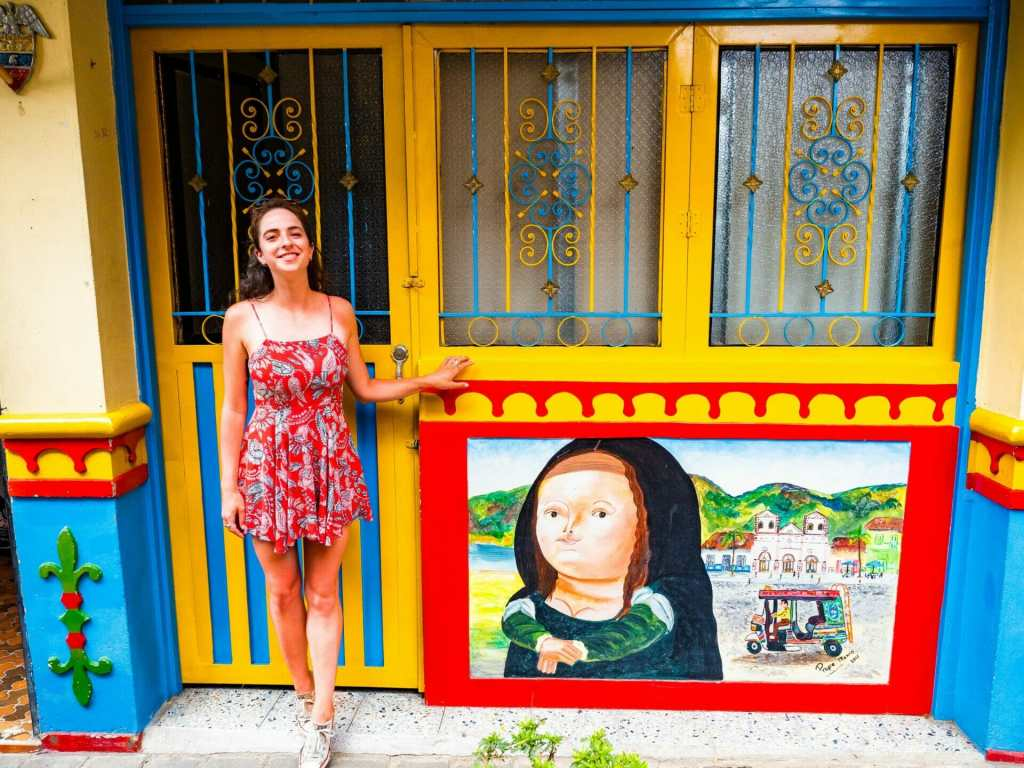 Girl outside colourful house zócalo painting Guatapé Colombia
