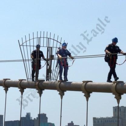 NYPD ESU officers climb down the Brooklyn Bridge. - Brooklyn Archive