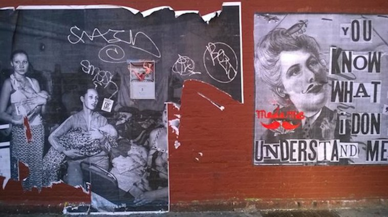 Two partially-ripped and graffiti-marked posters on a red brick wall in Brooklyn. One poster is a black-and-white photo of young women with babies; the other shows a caricature of a man's face alongside text in ransom-note style.