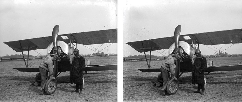 A selectively desaturated scan of two men working on a Nieuport 10, with someone (possibly the pilot) standing by.