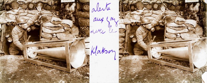 A Brentano's stereoview of a man in a gas mask poking out of a dugout, operating a huge hand-cranked klaxon horn