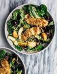 A healthful, Whole30-compliant avocado and mandarin orange salad topped with crisp sesame-crusted baked chicken tenders and drizzled with a creamy mandarin-ginger dressing.