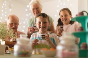 Happy multi-generation family eating cupcake at home for grandsons birthday