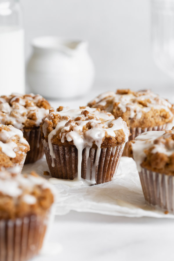 peach streusel muffins with glaze drizzled on top