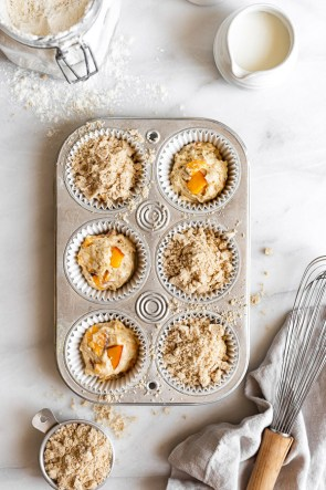 peach muffin batter in muffin tin with streusel on top