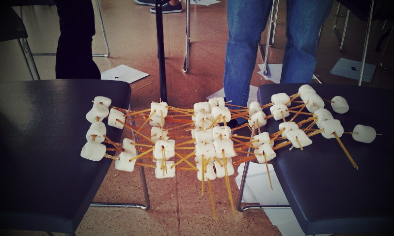Two black chairs propping up a bridge structure made of spaghetti and marshmallows. The structure spans over 1 foot between both chairs. The spaghetti is bundled together and stuck inside of the marshmallows.