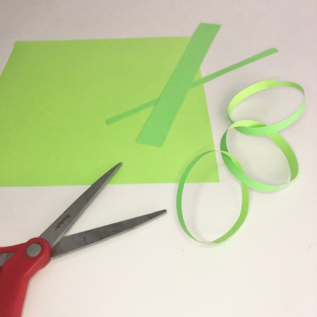 Easy to implement STEM for Distance Learning Activity. There is a green sheet of paper cut into small strips. The strips are turned into circles and chained together by tape. There is a pair of red scissors in the bottom left hand corner.