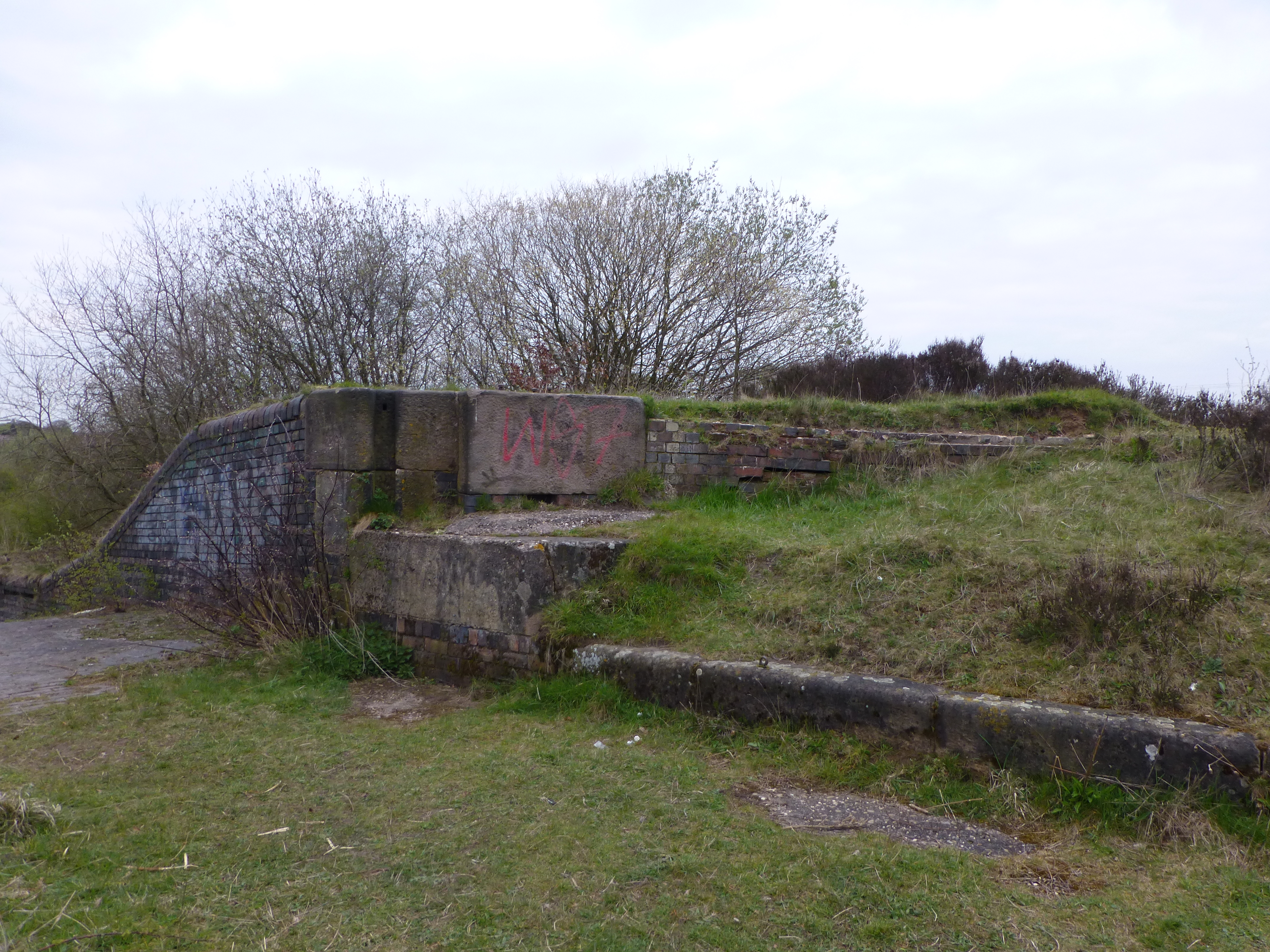 The upper main sluice gate post. These, we think, were like lock gates and retained a permanent pool in the spillway basin. The portal to the semicircular culvert is somewhere just to the right in the brickwork - the masonry is falling away due to the cavity below.