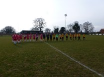 The teams line up before the start of the match , on an interesting pitch