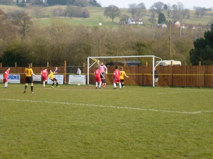 Alvechurch shoot at goal. With peaceful countryside in the distance