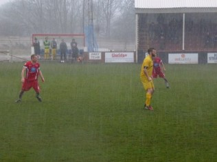 Both teams earn spectators' admiration and respect as play continues despite the sudden heavy rain and wind. Springtime soccer.