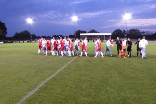The freshly watered grass glistened as players shake hands before play commenced