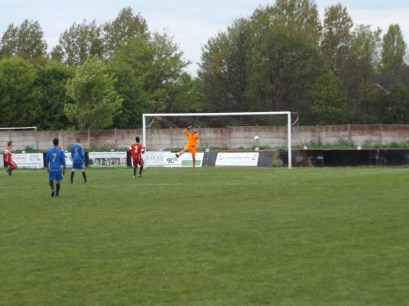 Tipton keeper reaches high to tip the incoming ball over the net. Fine skill.