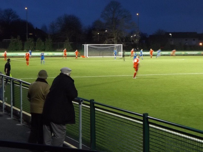 "Second half and Lichfield put the Wood under pressure as two ""Wood"" spectators, and the jolly linesman add a certain visual presence to the photograph."