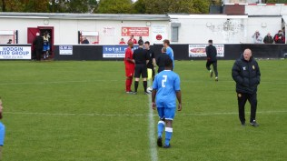 The captains shake hands before the start of the match. AFC played in blue