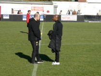 The two teams' managers, having shaken hands, take a moment to engage in pleasant conversation.