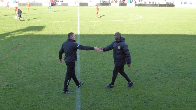 The match ends. Two managers shake hands.