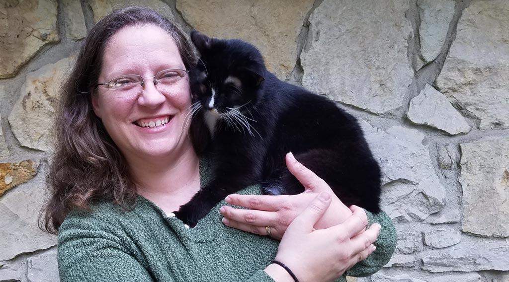 Kelli Barton, DVM, with her cat Copernicus on her shoulder