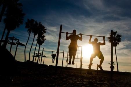 Two men do chin ups, Venice Beach, Los Angeles, California, USA