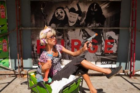 A person in front of ads on La Brea Ave., Los Angeles, California, USA