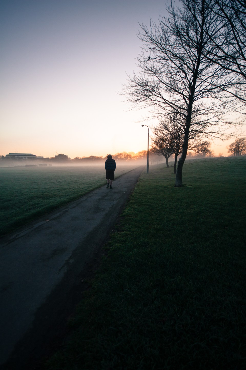 man walking towards the rising sun on a foggy morning