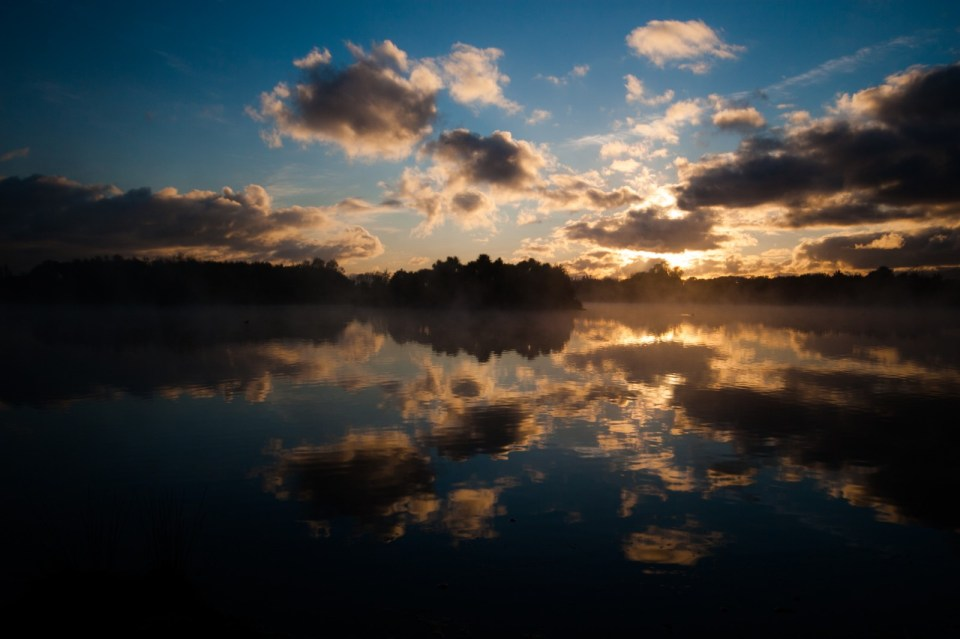 reflections of clouds in a pond with sun poking out from behind the clouds at sunrise