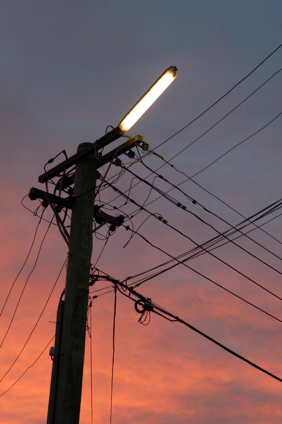 silhouetted power pole against a sunset sky