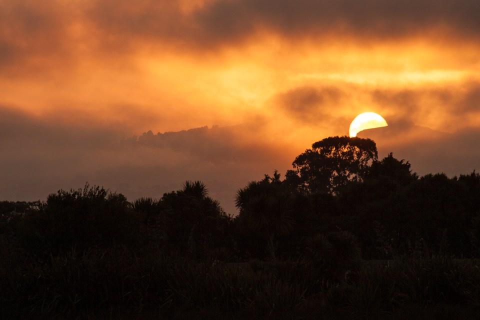 sun rising over hills