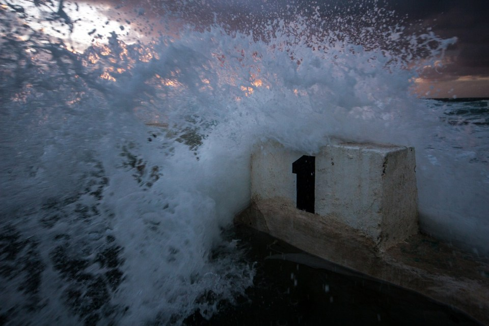 waves crashing over into the mereweather ocean baths, newcastle nsw