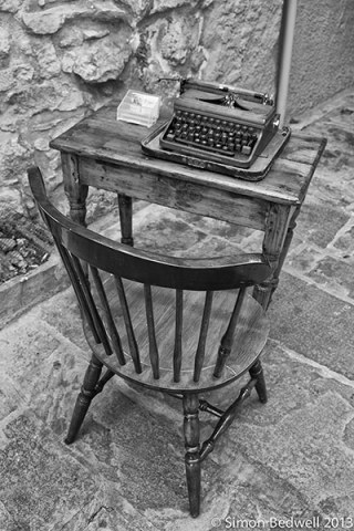 black and white picture of typewriter on desk with chair