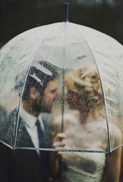 Bruidspaar onder transparante paraplu
