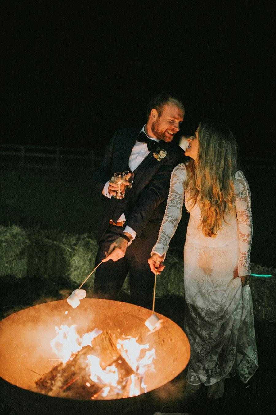Bruid en bruidegom maken s'mores bij kampvuur