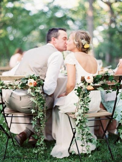 Bruidspaar op stoelen met stoeldecoratie