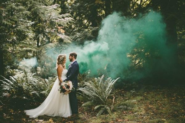 Bruidspaar in het bos met gekleurde rookbom