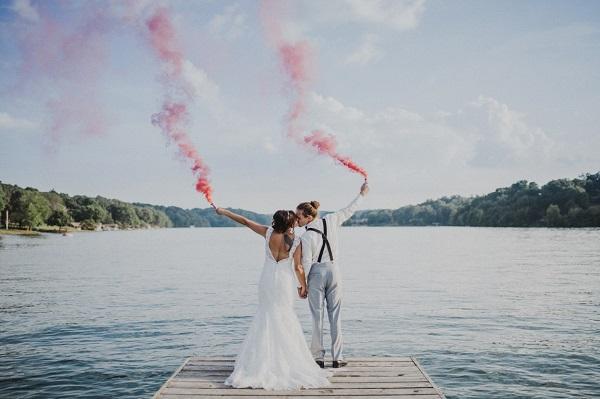 Bruidspaar aan het water met rookbommen