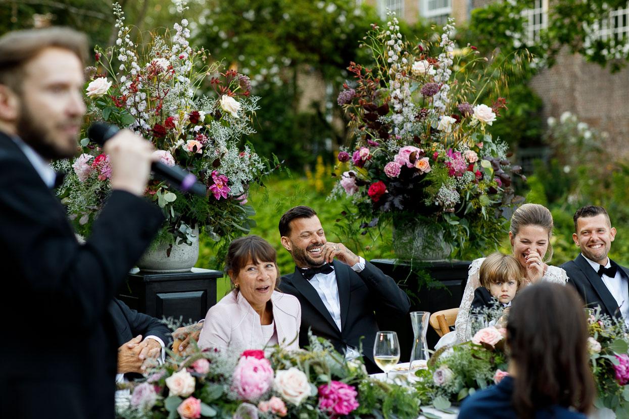 Lachend bruidspaar bij speech op de bruiloft