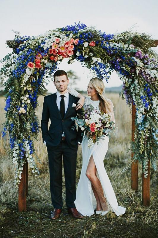 Bruidspaar onder trouwboog met bloemen