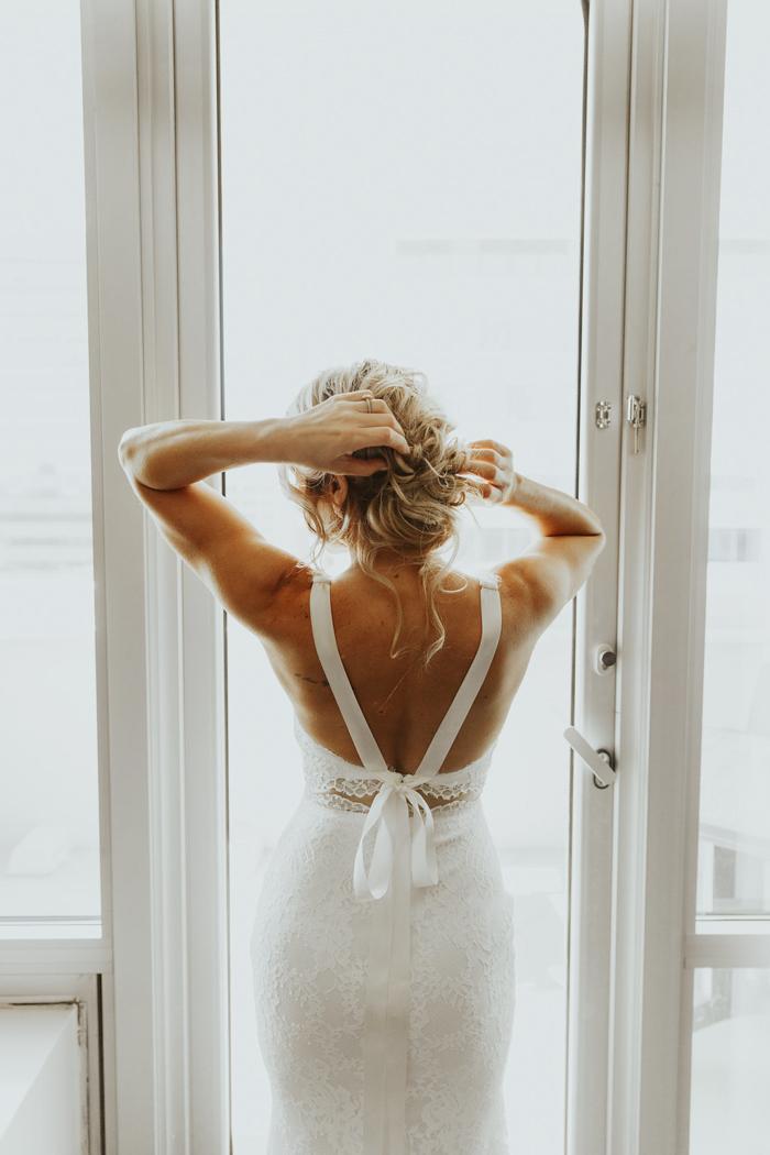 Bruid met twee in een trouwjurk voor het raam