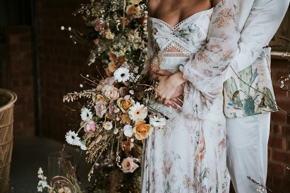 Bruidspaar met droogbloemen in bruidsboeket