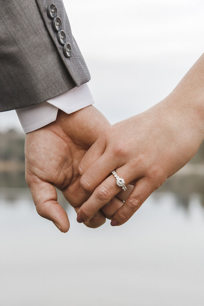 Bruidspaar hand in hand met verlovingsring