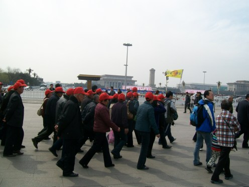 Anywhere in the world, it's easy to recognize Chinese and Japanese tour groups by their hats. This group at Tiananmen Square is wearing a red ball cap (some wear green, blue, or even pink).